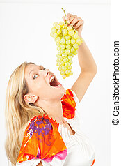 Eva mit Trauben - Junge Frau hält Weintrauben über ihren...
