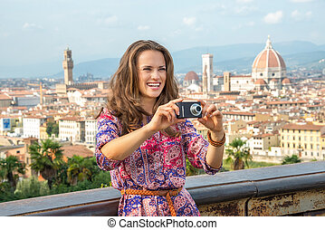 Smiling young woman taking photo against panoramic view of...