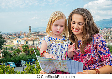 Happy mother and baby girl with map against panoramic view...