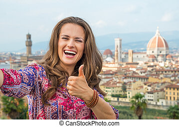 Happy young woman making selfie and showing thumbs up...