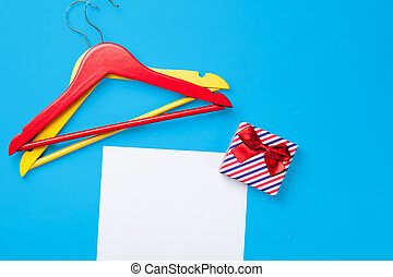 hangers and gift near paper on blue background