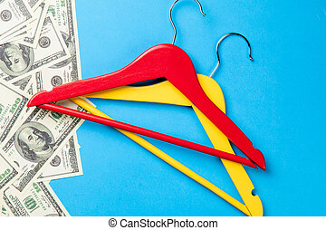 hangers and dollars near paper on blue background
