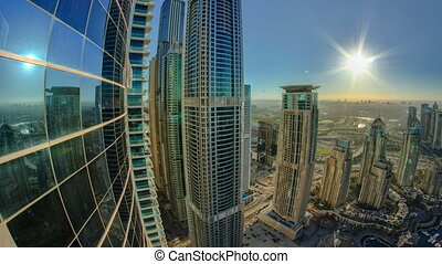 Modern skyscrapers in Dubai Marina with sun and reflection timelapse
