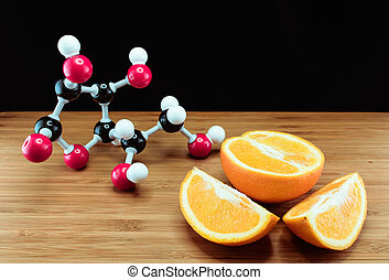 Orange and vitamin C structure model (Ascorbic acid) on wood...