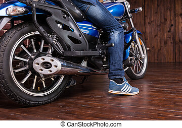 Man parking his motorbike indoors on a wooden floor with his...