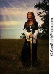 mystical medieval woman standing with a sword on a wild...