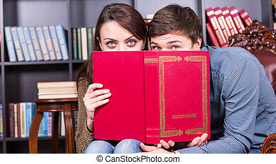 Young Couple Peeking Over a Red Book