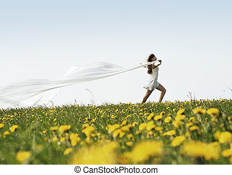 Young attractive girl with waving silk over sky background