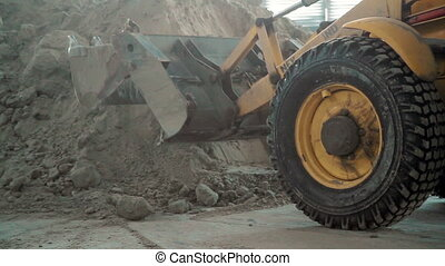 Bulldozer in warehouse work with sand