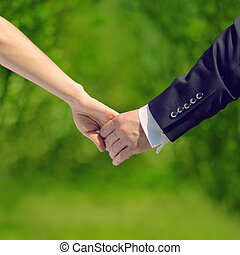 Wedding, love and relationships concept - sweet couple, hands br