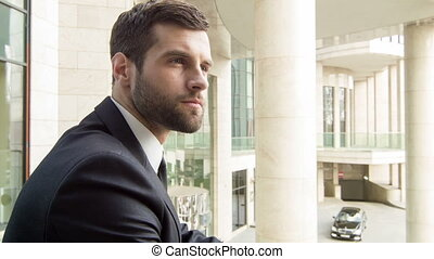 Young businessman standing at the terrace