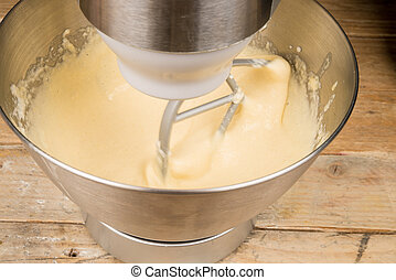 Food processor with beater tool preparing dough for a cake