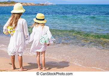 Adorable cute girls have fun on white beach during vacation...