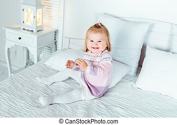 Funny and cute blond little laughing girl playing on bed in...