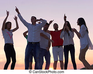 party people on sunset - group of happy young people dancing...