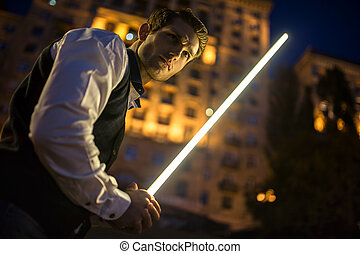 Handsome guy holding a lightsaber Jedi. Twilight in the...