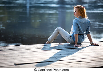 Red-haired girl with blue eyes sitting on a wooden pavement...