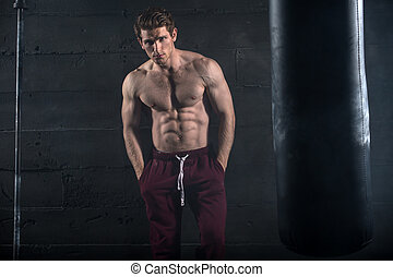 Athletic man with naked torso near concrete wall in the...