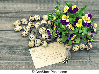 easter decoration with pansy flowers, quail eggs and...