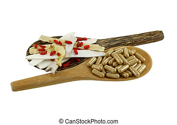Chinese medical herb and capsules - A wooden spoon full of...