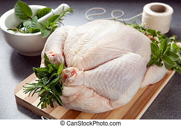 Preparing Chicken for Roasting - Raw chicken on a board,...