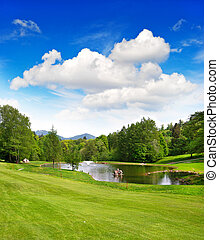 golf field with beautiful blue sky and lake