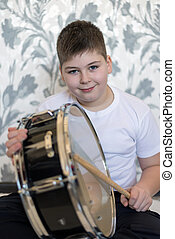 Teenager boy with a drum in  room