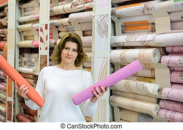 Woman buys wallpaper in store - A Woman buys wallpaper in...