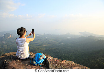 woman hiker taking photo - woman hiker taking photo with...