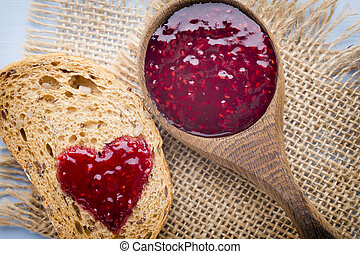 Jam. - Grain slice of bread with jam heart shape.