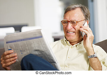 Senior man reading stock listings and talking on mobile...