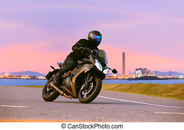 young man riding sport touring motorcycle on asphalt...