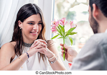 Boy giving flower to girl in restaurant.