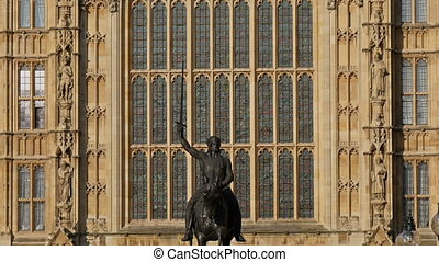A monument of a man riding a horse infront of the Palace of...