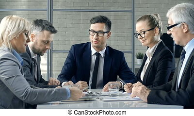 Board Meeting - Close up of five business people discussing...