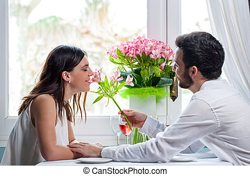 Young man giving flower to girlfriend in restaurant.