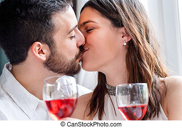 Romantic couple kissing at dinner - Close up face shot of...