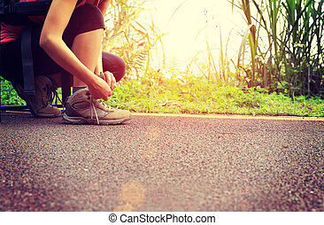 young woman hiker tying shoelaces in the nature