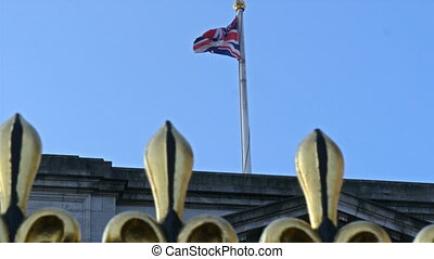 The flag of England on a pole of the Buckingham Palace The...
