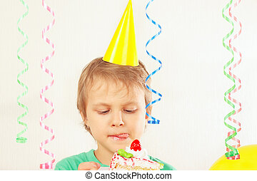 Young child in festive hat tasting piece of birthday cake