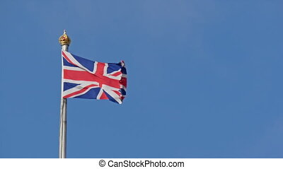 The England flag waving on the pole. It waves on the breeze...