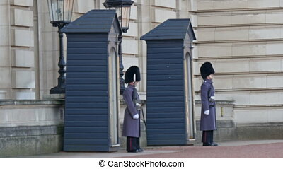 Four guards with coat standing on their posts The guards are...