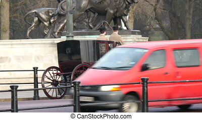 A horse carriage with a lady and a man on it. Travelling on...