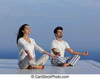 young couple practicing yoga at sunset in modern home terace...