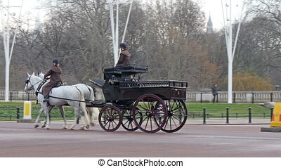 Three horse carriages on the street of the Palace One guard...