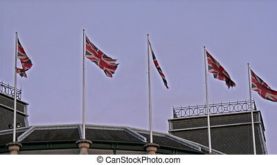 Five England flags waving on the flag poles