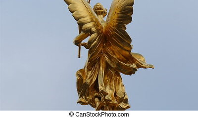 The golden angel statue infront of the palace. Seen are the...