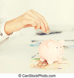woman hand putting coin into small piggy bank - business,...