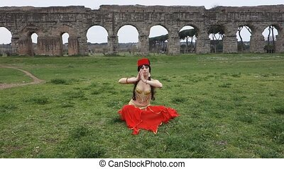 belly dancer slow-motion with ancient Roman aqueducts ruins...