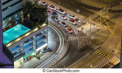 Traffic on intersection with tram at night timelapse from top, Dubai Marina